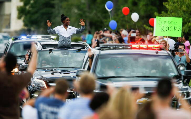 Gymnast Simone Biles waives to fans as she is welcomed home with a small parade along Rayford Road Wednesday, August 24, 2016 in Spring after winning four gold medals and a bronze at the Olympics in Rio de Janeiro.