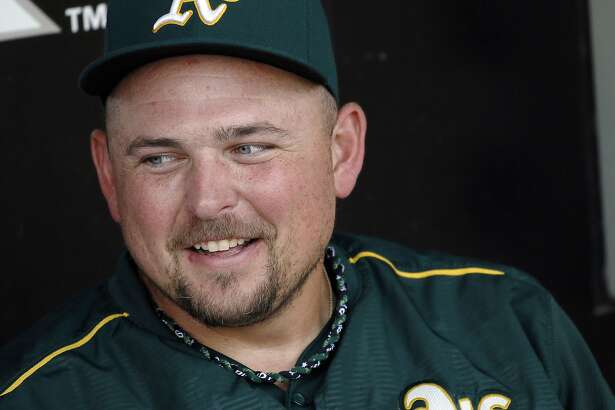 FILE - In this Sept. 17, 2015, file photo, Oakland Athletics designated hitter Billy Butler gives an interview in the dugout after a baseball game against the White Sox in Chicago.The 29-year-old Butler is confident his intense regimen all winter in Arizona will only benefit him early in spring training after he was limited last year at this time because of wrist injuries that didn�t allow him to swing a bat right away. (AP Photo/Andrew A. Nelles, File)