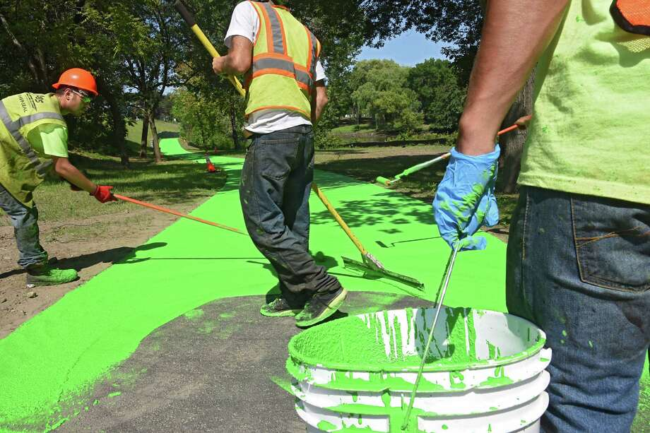 Employees for Luizzi Bros. Sealcoating & Striping lay down a green coat of Color Safe on the new stretch of bike path in the Corning Preserve on Wednesday, Aug. 24, 2016 in Albany, N.Y. The surface is a skid-resistant resin. (Lori Van Buren / Times Union) Photo: Lori Van Buren / 20037770A