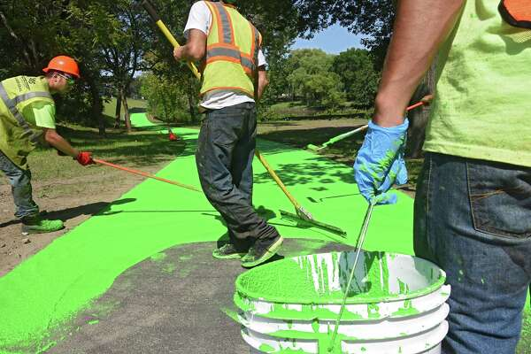 Employees for Luizzi Bros. Sealcoating & Striping lay down a green coat of Color Safe on the new stretch of bike path in the Corning Preserve on Wednesday, Aug. 24, 2016 in Albany, N.Y. The surface is a skid-resistant resin. (Lori Van Buren / Times Union)