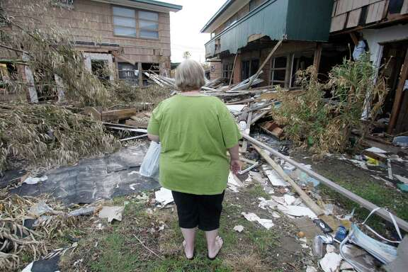 Galveston resident Patricia Davis, 53, surveys her badly damaged apartment after arriving home for the first time Wednesday, Sept. 24, 2008, in Galveston, Texas. Thousands of people returned on Wednesday for the first time since their island city was blasted by Hurricane Ike nearly two weeks ago. (AP Photo/Rick Bowmer)