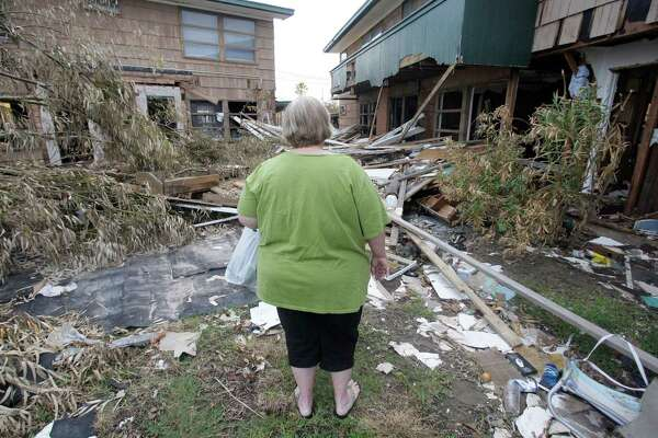 A Galveston resident looks over her wreck apartment complex after Hurricane Ike. TWIA says rates did not need to be raised.