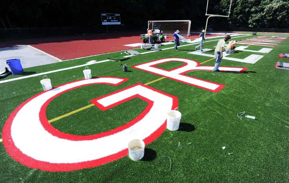 """Workers from the Sprinturf Company headquartered in Atlanta, Ga., install the end zone lettering the reads """"GREENWICH"""" for the new artificial turf field at Greenwich High School's Cardinal Stadium, Conn., Wednesday afternoon, Aug. 24, 2016. Tim Karca, pictured here at right, who was supervising and who was one of six workers who have been installing the field for the past three weeks said, """" We should be finished in a couple of days. It should be ready to be opened next Wednesday.""""  Karca when asked what makes this turf field special responded """"The infill for the field is environmentally safe. It is also cooler because the sand coated plastic reflects heats."""" Photo: Bob Luckey Jr. / Hearst Connecticut Media / Greenwich Time"""