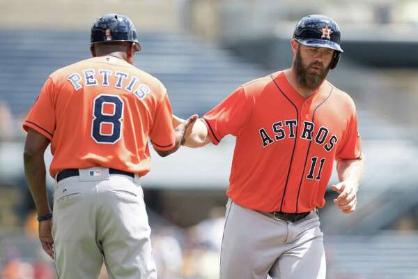 PITTSBURGH, PA - AUGUST 24:  Evan Gattis #11 of the Houston Astros is greeted by third base coach Gary Pettis #8 after hitting a two-run home run in the second inning during the game against the Pittsburgh Pirates at PNC Park on August 24, 2016 in Pittsburgh, Pennsylvania.