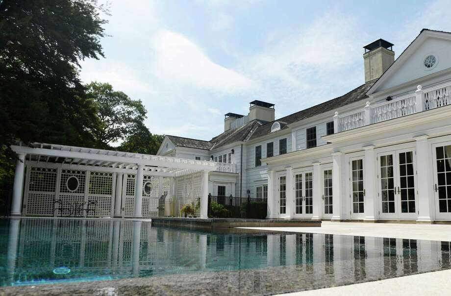 """An infinity edge pool and gazebo at the rear of the """"Azalea Hill"""" Georgian manor estate at 167 Zaccheus Mead Lane in Greenwich. The 13,318 sq. ft. home sits on four acres of land and features six bedrooms, 11 bathrooms, an infinity edge pool, fireplaces and handpainted murals in a design that blends traditional and modern elements. Photo: Tyler Sizemore / Hearst Connecticut Media / Greenwich Time"""