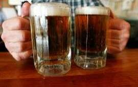 FILE - In this Tuesday, June 29, 2004 file photo, a bartender serves two mugs of beer at a tavern in Montpelier, Vt. College-age drinkers average nine drinks when they get drunk, government health officials said Tuesday, Jan. 10, 2012. That surprising statistic is part of a new report highlighting the dangers of binge drinking, which usually means four to five drinks at a time. Overall, about 1 in 6 U.S. adults surveyed said they had binged on alcohol at least once in the previous month, though it was more than 1 in 4 for those ages 18 to 34. And that's likely an underestimate. (AP Photo/Toby Talbot)