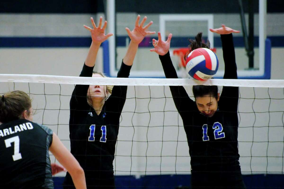 Friendswood's Faith Marabella (11) and Friendswood's Natalie Abowd (12) go high to block a shot by Pearland's Brooke Botkin (7) Tuesday, Aug. 23.
