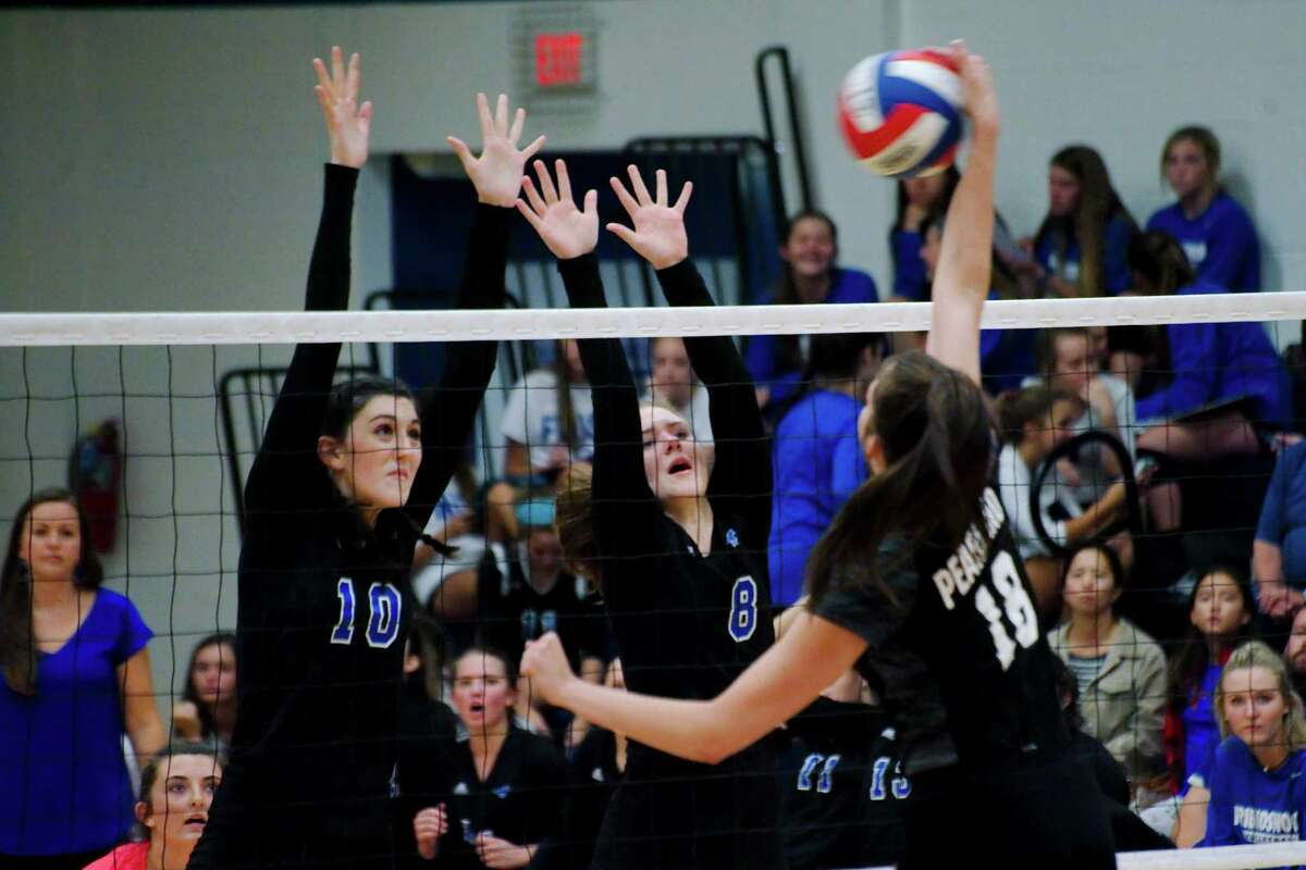 Friendswood's McKenna Fridye (10) and Friendswood's Jenna Chenette (8) go high to block a shot from Pearland's Sam Costello (18) Tuesday, Aug. 23.