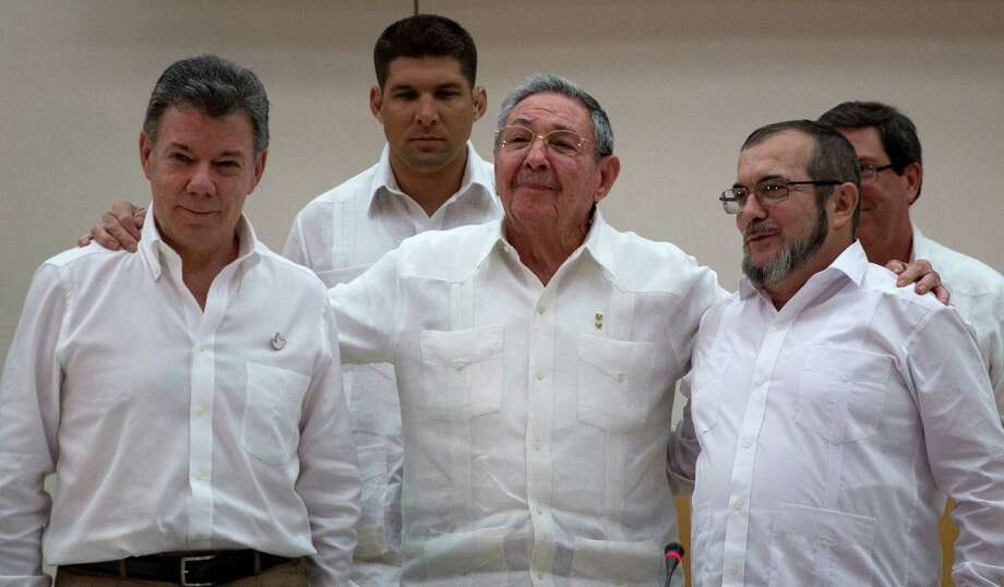 FILE - In this Sept. 23, 2015 file photo, Cuba's President Raul Castro, center, stands with Colombian President Juan Manuel Santos, left, and Commander the Revolutionary Armed Forces of Colombia or FARC, Timoleon Jimenez , in Havana, Cuba.  Negotiators for Colombia's government and leftist rebels are putting the final touches on a historic peace deal that they hope to announce in the coming hours. Several government negotiators told local news media on Wednesday, Aug. 24, 2016, that all major obstacles to a deal have been cleared up in around-the-clock sessions taking place in Cuba. (AP Photo/Desmond Boylan, File) Photo: Desmond Boylan, STR / Copyright 2016 The Associated Press. All rights reserved. This material may not be published, broadcast, rewritten or redistribu