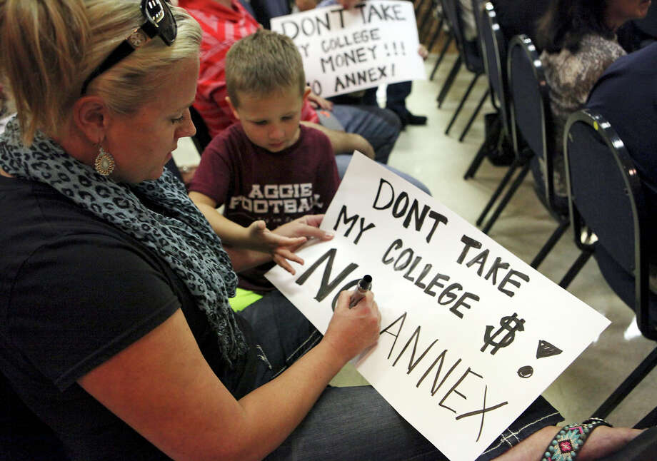 Kristy Newson and her son Kaiden Newson, 5, make a sign Oct. 15, 2015, before an anti-annexation forum organized by two emergency services districts at the Crown Ridge Banquet Hall. The area near Interstate 10 West is slated for annexation. Photo: Edward A. Ornelas /San Antonio Express-News / © 2015 San Antonio Express-News