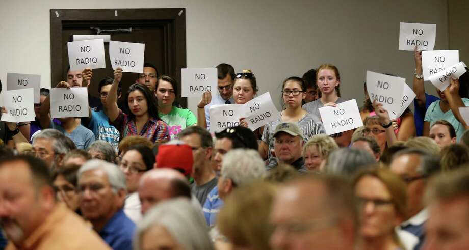 Signs are raised against the proposed partnership between he Sequin Independent School District and Guadalupe Media during a special meeting on the subject. Photo: Jerry Lara / San Antonio Express-News / © 2016 San Antonio Express-News