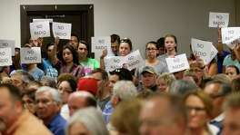 Signs are raised against the proposed partnership between he Sequin Independent School District and Guadalupe Media during a special meeting on the subject.
