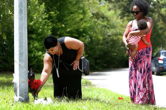 Kimberly Bass on Wednesday lays a vase of flowers at the scene where her 85-year-old father died after a car struck him on his bike around 11 p.m. Monday in the 700 block of West 43rd Street near Shepherd. Bass said her father was independent and spiritual.