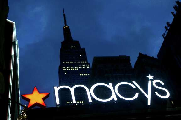FILE - In this Nov. 21, 2013, file photo, with the Empire State building in the background, the Macy's logo is illuminated on the front of the department store in New York. It turns out there's a wealth gap among companies, just like among people. Of the $1.8 trillion in cash that's sitting in U.S. corporate accounts, half of it belongs to just 25 of the 2,000 companies tracked by S&P Global Ratings.  In March 2016, S&P cut its ratings on Macy's to BBB, two notches above junk, as competition from internet retailers continues to dig into the department store chain's sales. (AP Photo/Mark Lennihan, File)