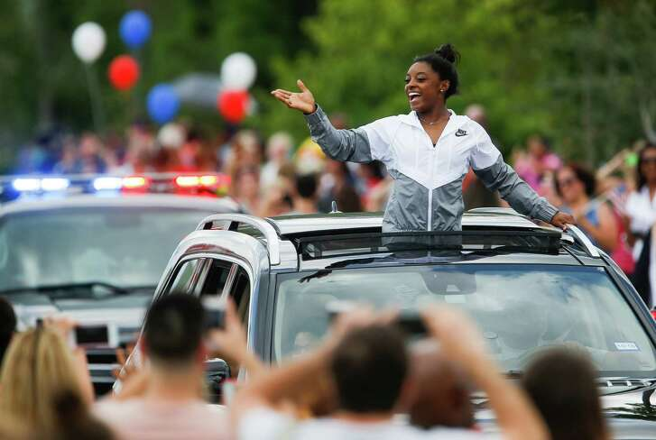 Simone Biles treated fans to her trademark smile and energy during a welcome-home parade in Spring.