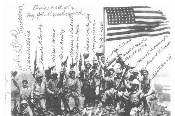 "After the second flag-raising on Iwo Jima's Mount Suribachi, this ""gung ho"" photograph was taken. There is no photograph of the first flag-raising."