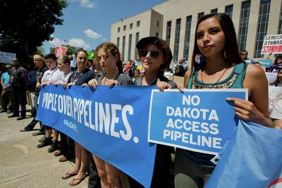 Actresses Shailene Woodley, fourth from right, and Susan Sarandon, second from right, and Standing Rock Sioux Tribe member Bobbi Jean Three Lakes, right, protest the  Dakota Access Pipeline at a rally Wednesday.