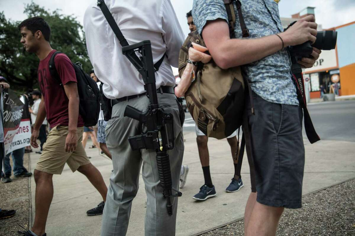 Andrew Clements, openly carries an AR-15 on a public street at the edge of the University of Texas at Austin campus during a rally at the school protesting a new law allowing concealed weapons on the state's college campuses, in Austin, Texas, Aug. 24, 2016. Students planned to carry sex toys openly to class, attached to their backpacks, to show that they feel guns have no place on campus and could stifle the open exchange of ideas. (Tamir Kalifa/The New York Times)