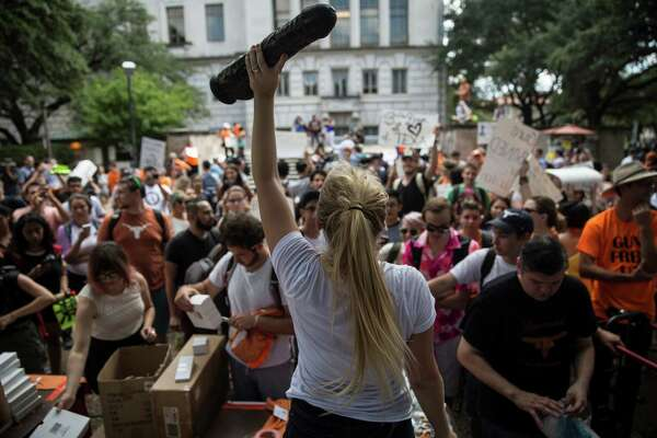 "Student Rosie Zander waves a sex toy during a rally on the first day of classes at University of Texas at Austin, a protest of a new law that allows concealed handguns on the state's college campuses, in Austin, Texas, Aug. 24, 2016. ÒThese laws wonÕt protect anyone,"" said a protest organizer,"" Jessica Jin. ÒItÕs absurd. So, I thought, we have to fight absurdity with absurdity,Ó he said, explaining why many students carried dildos as part of the protest. (Tamir Kalifa/The New York Times)"