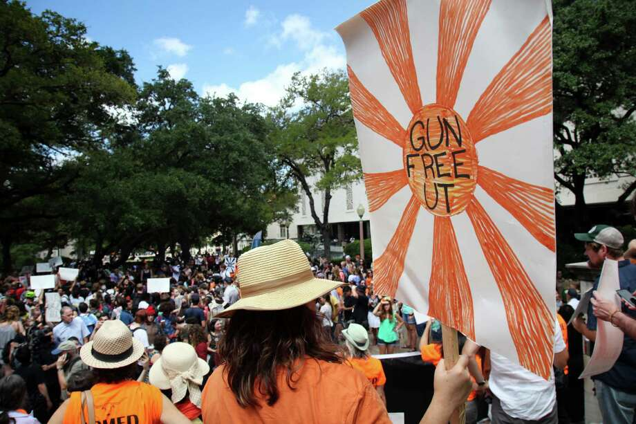 "FILE - A protester carries a sign calling for a ""Gun Free UT"", as they join others during a protest on campus in Austin, Texas on Aug. 24, 2016. Early Thursday, Students for Concealed Carry responded to news of UT Police finding unattended firearms in a school bathroom. Photo: John Mone, Associated Press / Copyright 2016 The Associated Press. All rights reserved. This material may not be published, broadcast, rewritten or redistribu"