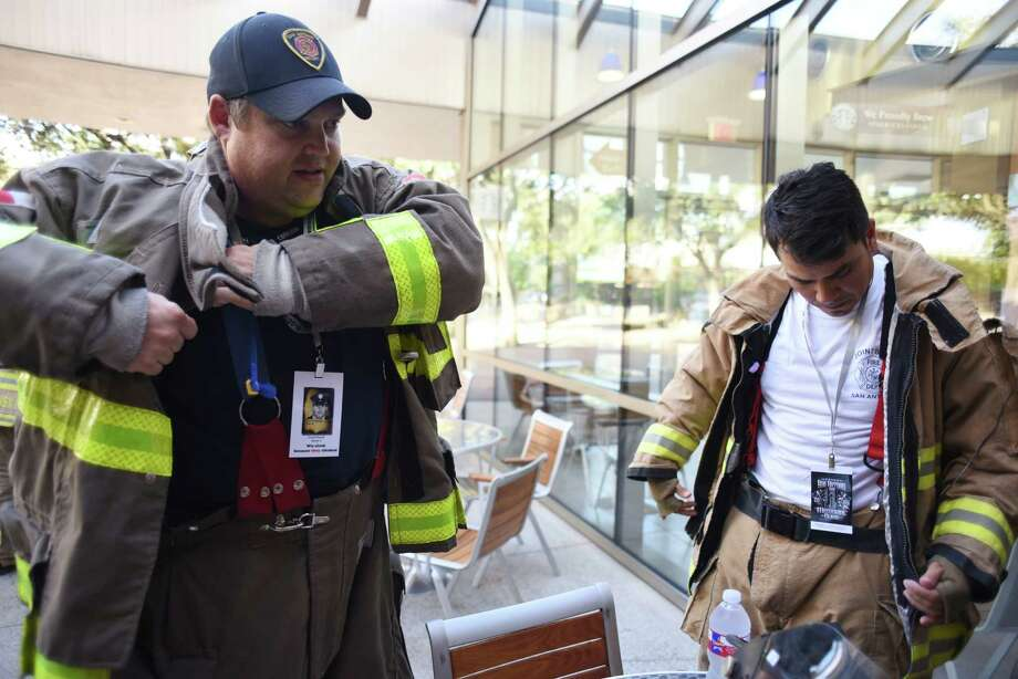 Firefighters Chad Sharron, left, and Abel Campos don their gear in preparation for the San Antonio 110 9/11 Memorial Climb committee's climb up the Tower of the Americas stairs on Wednesday, Aug. 24, 2016, in honor of fallen New York firefighters who lost their lives on Sept. 11, 2001. The committee members climbed so that on September 11, when the actual event takes place, they can act as organizers and guides for the hundreds of people expected to climb the tower stairs on that day. Photo: Billy Calzada, Staff / San Antonio Express-News / San Antonio Express-News