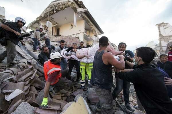 A woman is pulled out of the rubble following an earthquake in Amatrice Italy, Wednesday, Aug. 24, 2016.  The magnitude 6 quake struck at 3:36 a.m. (0136 GMT) and was felt across a broad swath of central Italy, including Rome where residents of the capital felt a long swaying followed by aftershocks. (Massimo Percossi/ANSA via AP) ORG XMIT: ROM103