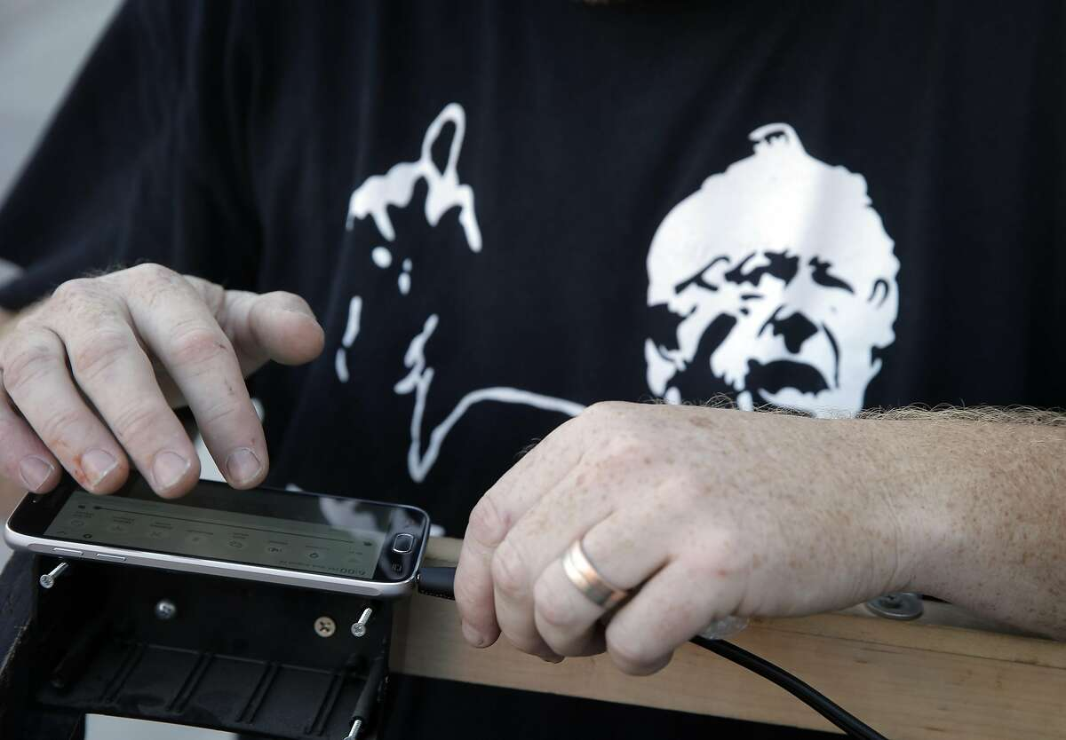 """Event organizer, John Pomeroy checks the status of the live stream on his phone during a watch party the Soundwave Studios in Oakland, Calif., on Wednesday, August 24, 2016, where supporters listened to Bernie Sanders announcing in detail what the next step of his """"political revolution."""""""