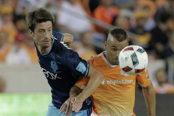 Houston Dynamo midfielder Alex (14) and Seattle Sounders defender Zach Scott (20) go for the ball during  MLS game action on Wednesday, Aug. 24, 2016, in Houston. ( Elizabeth Conley / Houston Chronicle )