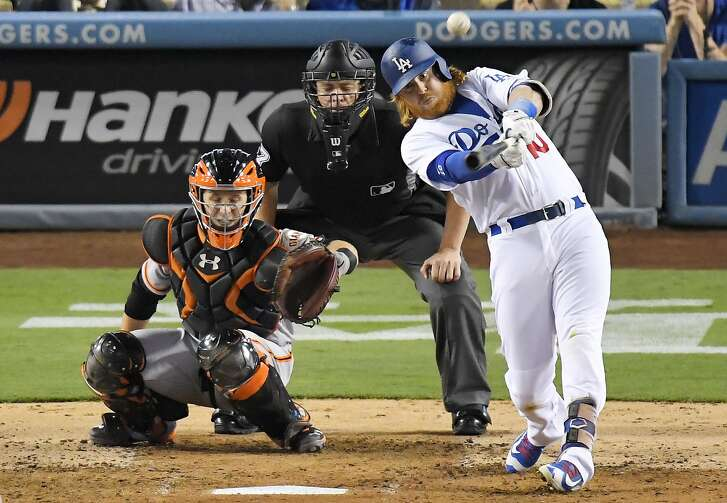 Los Angeles Dodgers' Justin Turner hits a solo home run as San Francisco Giants catcher Buster Posey, left, watches along with home plate umpire Carlos Torres during the fourth inning of a baseball game, Wednesday, Aug. 24, 2016, in Los Angeles. (AP Photo/Mark J. Terrill)