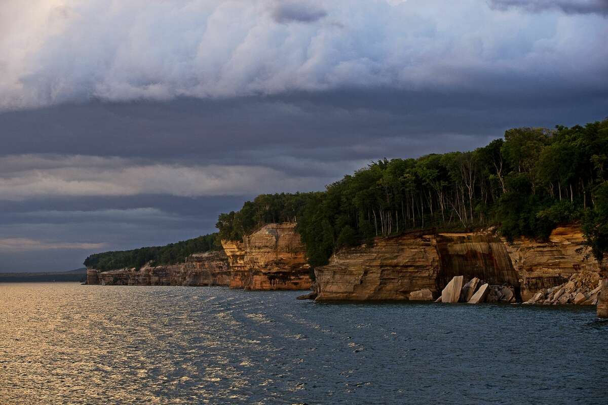 FILE - Rock formations are illuminated by sunlight at Pictured Rocks National Lakeshore on July 13, 2016. Pictured Rocks is known for its 42 miles of lakeshore complete with dusty-colored rock cliffs, waterfalls, and sand dunes.
