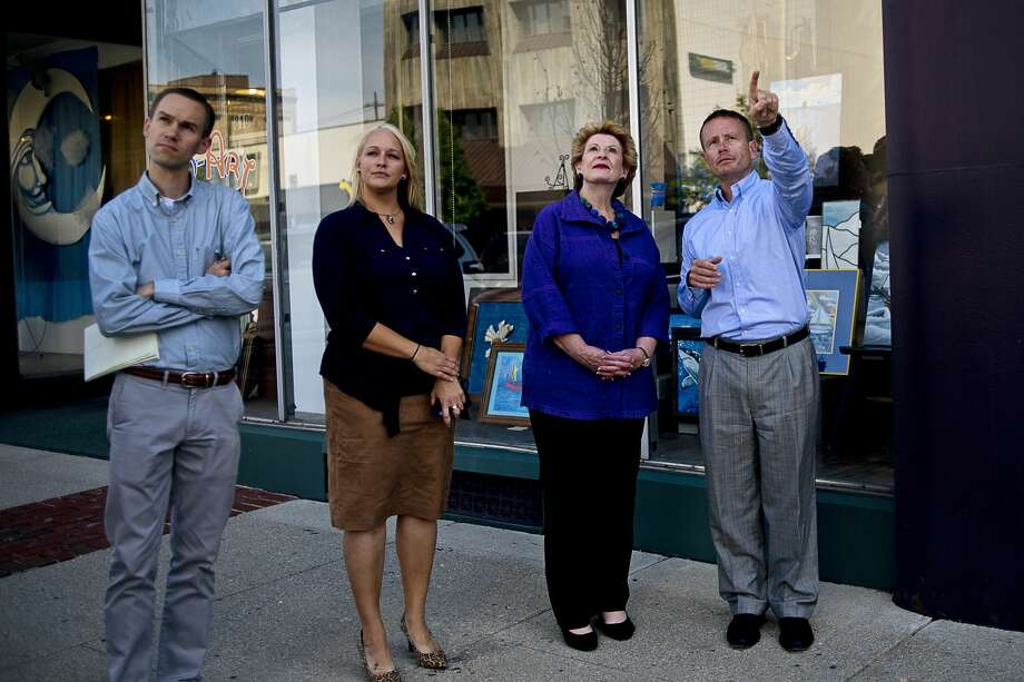 From left, Bay City Times reporter Andrew Dodson, Bay Area Chamber of Commerce Vice President Jesse Pero, U.S. Senator Debbie Stabenow and Bay Area Chamber of Commerce President Ryan Carley look at various Bay City downtown buildings during Stabenow's small business tour in Bay City on Wednesday. Stabenow has been traveling throughout the state to meet and greet small business owners and entrepreneurs who employed 1.8 million of the state's private workforce in 2012. Photo: Erin Kirkland/Midland Daily News