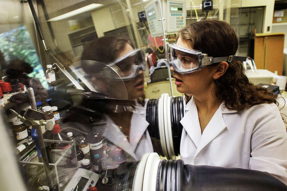 THEOPHIL SYSLO | For the Daily News Midland High School senior Brittney Duford, 17, uses a glove box, a nitrogen-filled enclosure, to perform reactions in an air and moisture sensitive environment at Michigan State University's new STEM center in Midland on Thursday.  For more photos, see page C1.