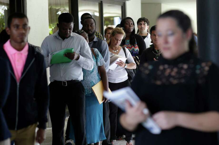 People stand in line to apply for a job with Aldi at a job fair in Miami Lakes, Fla. The number of applications for jobless benefits has remained below 300,000 for 77 straight weeks, the longest streak since 1970. The current reading is even more impressive because the population has grown considerably since then. Photo: Lynne Sladky /Associated Press / Copyright 2016 The Associated Press. All rights reserved. This material may not be published, broadcast, rewritten or redistribu