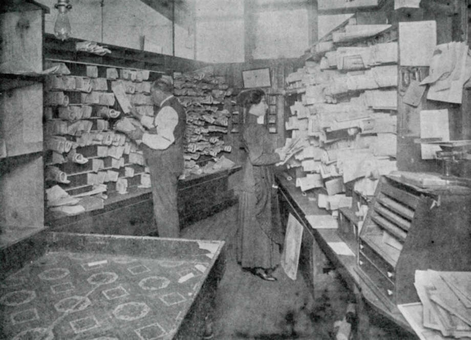 Post Office circa 1905. It was located at 134 E. Main St., formerly LaSalle Cafe. Henry D. Northway was postmaster and is shown being assisted by Maude (Brooks) Lee.