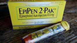 Mylan, now in the cross hairs over severe price hikes for its EpiPen, said Thursday it will expand programs that lower out-of-pocket costs by as much as half.