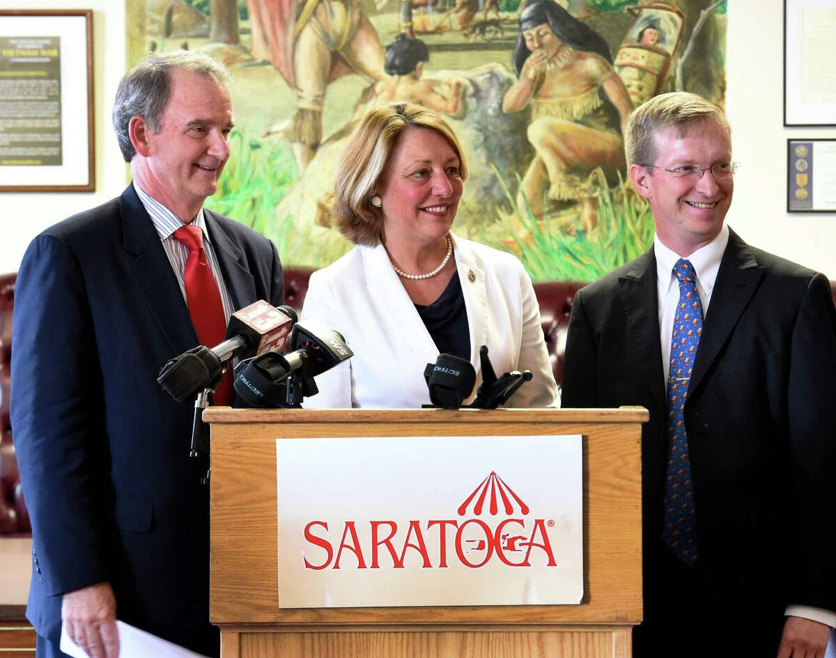 NYRA CEO Chris Kay, left joins Mayor Joanne Yepsen and Todd Shimkus, president, Saratoga Chamber of Commerce, right Monday afternoon July 13, 2015 to announce that August 5th will be free admission at the Saratoga Race Course in honor of the 100th anniversary of the birth of the City of Saratoga Springs. (Skip Dickstein/Times Union)