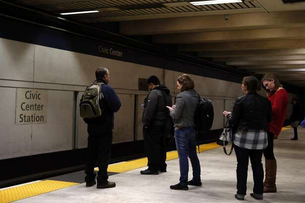 Commuters await a train at Civic Center BART station in San Francisco, Calif., on Wednesday, November 26, 2014.