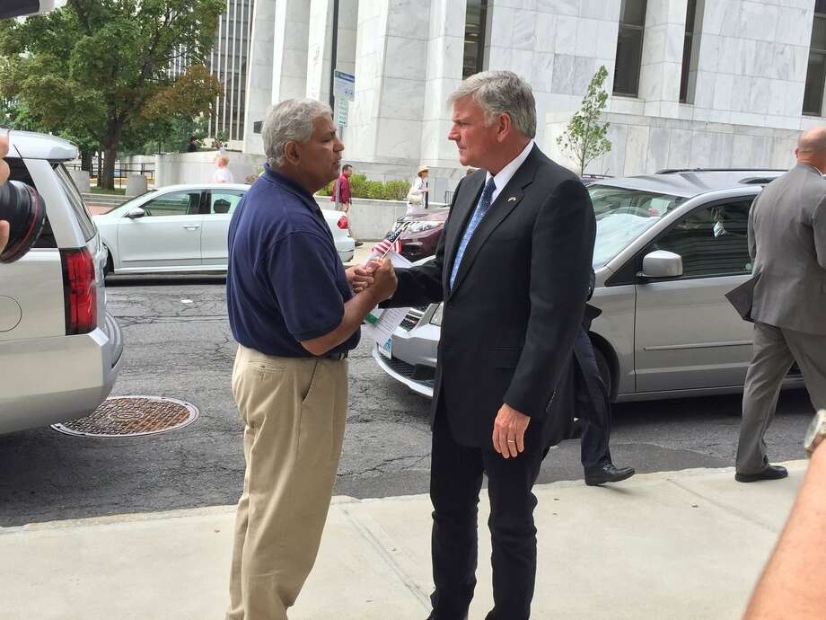 Rev. Franklin Graham, right, greets a man after speaking to reporters in Albany on Thursday. Graham was set to speak at a noon rally outside the Capitol. (Matt Hamilton / Times Union)