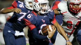 Roosevelt quarterback Bryson Carroll (center) looks for running room during the first half of their game with Judson at Heroes Stadium on Sept. 11, 2015.