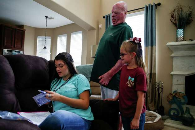 Karlee Smith helps open a popcorn bag for her father, Mike Smith, who was severally injured in an explosion at Air Liquid in 2013, Monday, August 22, 2016 in Pearland. After his burns healed, skin grew and fused between his fingers, majorly limiting their mobility and making some seemingly easy tasks incredibly difficult. Photo: Michael Ciaglo, Houston Chronicle / © 2016  Houston Chronicle