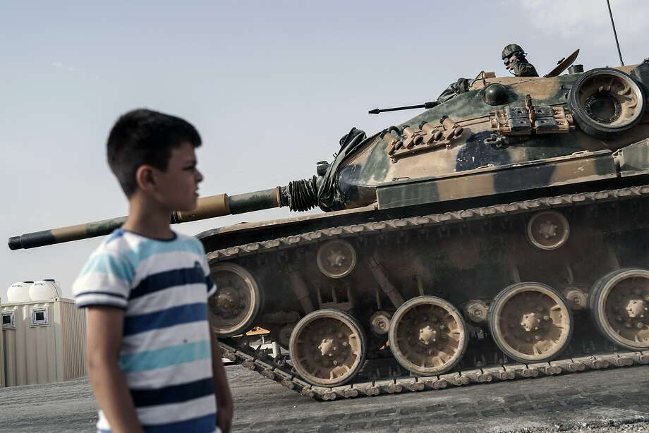 A boy looks at Turkish army tanks and armored personnel carriers moving toward the Syrian border, in Karkamis, Turkey. Photo: Halit Onur Sandal, Associated Press