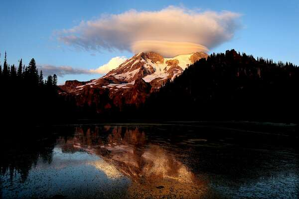 FILE - In this September 2012, file photo, a cloud hovers over Mount Rainier at sunset in a view from Klapatche Park Camp at Mount Rainier National Park, Wash. An active volcano, Mount Rainier is the most glaciated peak in the contiguous United States, according to the National Parks Service. (Drew Perine/The News Tribune via AP, File)