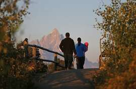 Kimberly Quaide and her husband Michael walk with their baby Madeline, watching as the sun at dawn illuminates mountain peaks as seen from Signal Mountain in Grand Teton National Park, Wyo., Thursday, Aug 25, 2016. Thursday marks the 100th anniversary of the National Park Service. (AP Photo/Brennan Linsley)