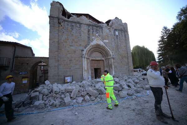 People stand in front of a damaged church in Amatrice on August 24, 2016 after a powerful earthquake rocked central Italy. The earthquake left 38 people dead and the total is likely to rise, the country's civil protection unit said in the first official death toll. Scores of buildings were reduced to dusty piles of masonry in communities close to the epicentre of the quake, which had a magnitude of between 6.0 and 6.2, according to monitors. / AFP PHOTO / FILIPPO MONTEFORTEFILIPPO MONTEFORTE/AFP/Getty Images