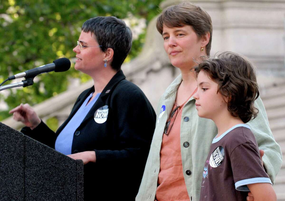 Times Union staff photo by Cindy Schultz -- Elissa Kane of Albany, right, speaks with partner Lynne Lekakis, center, and their daughter (family does not want child identified) joining her at the podium during a rally to support same sex marriage and protest the court's decision Thursday, July 6, 2006, at the state Capitol in Albany, N.Y. (WITH STORY)
