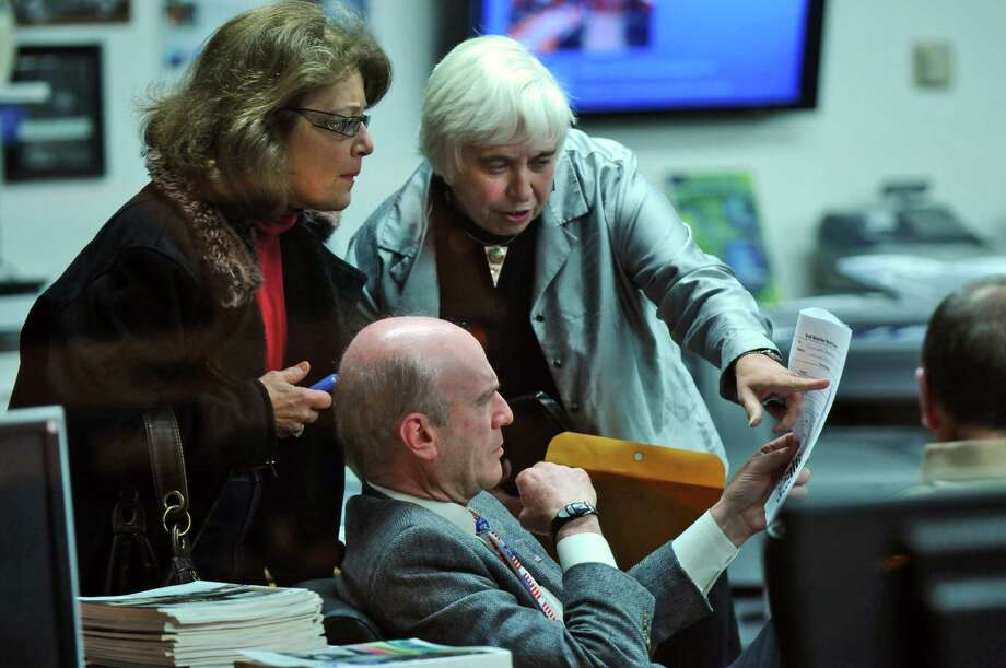 Schenectady Mayoral candidate Roger Hull goes over election returns from the Stockade district with volunteers Mary Ellen Brockbank, left, and Cathy Lewis, right, on Tuesday night Nov. 8, 2011 in Schenectady, NY.  (Philip Kamrass / Times Union ) Photo: Philip Kamrass / 00015305A