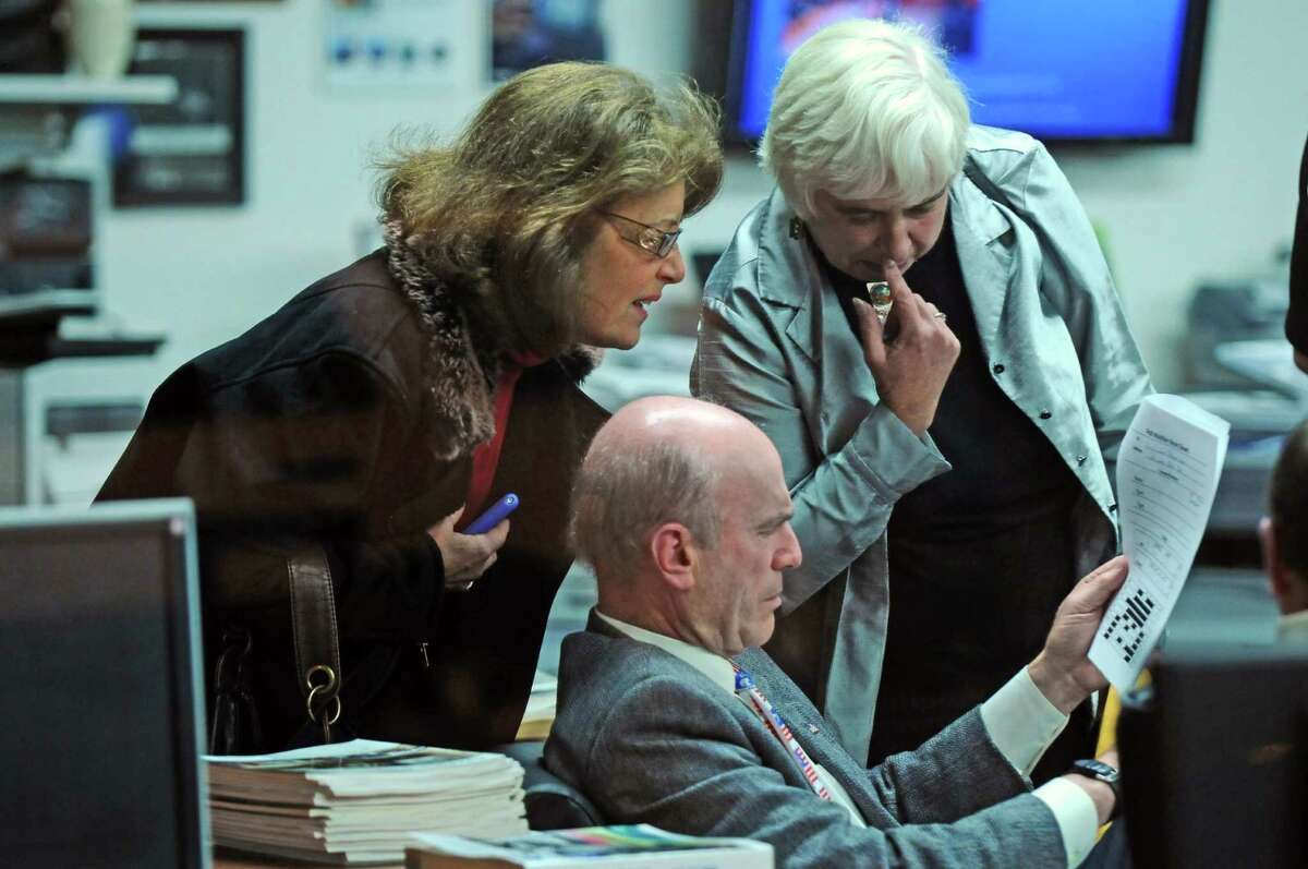 Schenectady Mayoral candidate Roger Hull goes over election returns from the Stockade district with volunteers Mary Ellen Brockbank, left, and Cathy Lewis, right, on Tuesday night Nov. 8, 2011 in Schenectady, NY. (Philip Kamrass / Times Union )