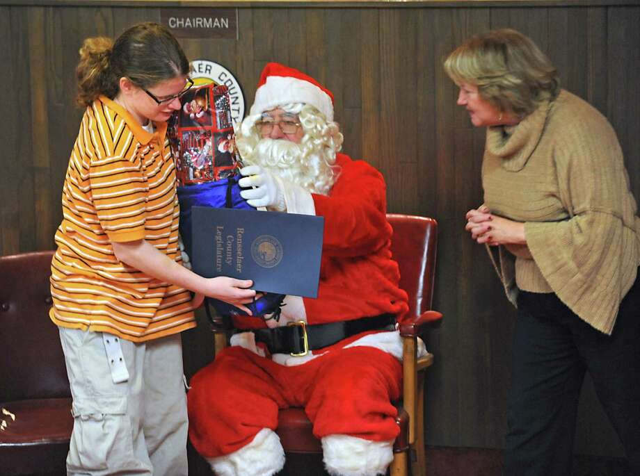 20-year-old Ashley (who's name we can't publish),of the Vanderheyden Hall youth residential facility, receives some gifts from Santa during The Vanderheyden Christmas party at the chambers of the County Legislature in Troy , NY on December 17, 2010. Judy Breselor, Rensselaer County Legislature District 4, plays Santa's helper.  (Lori Van Buren / Times Union) Photo: Lori Van Buren / 00011466A