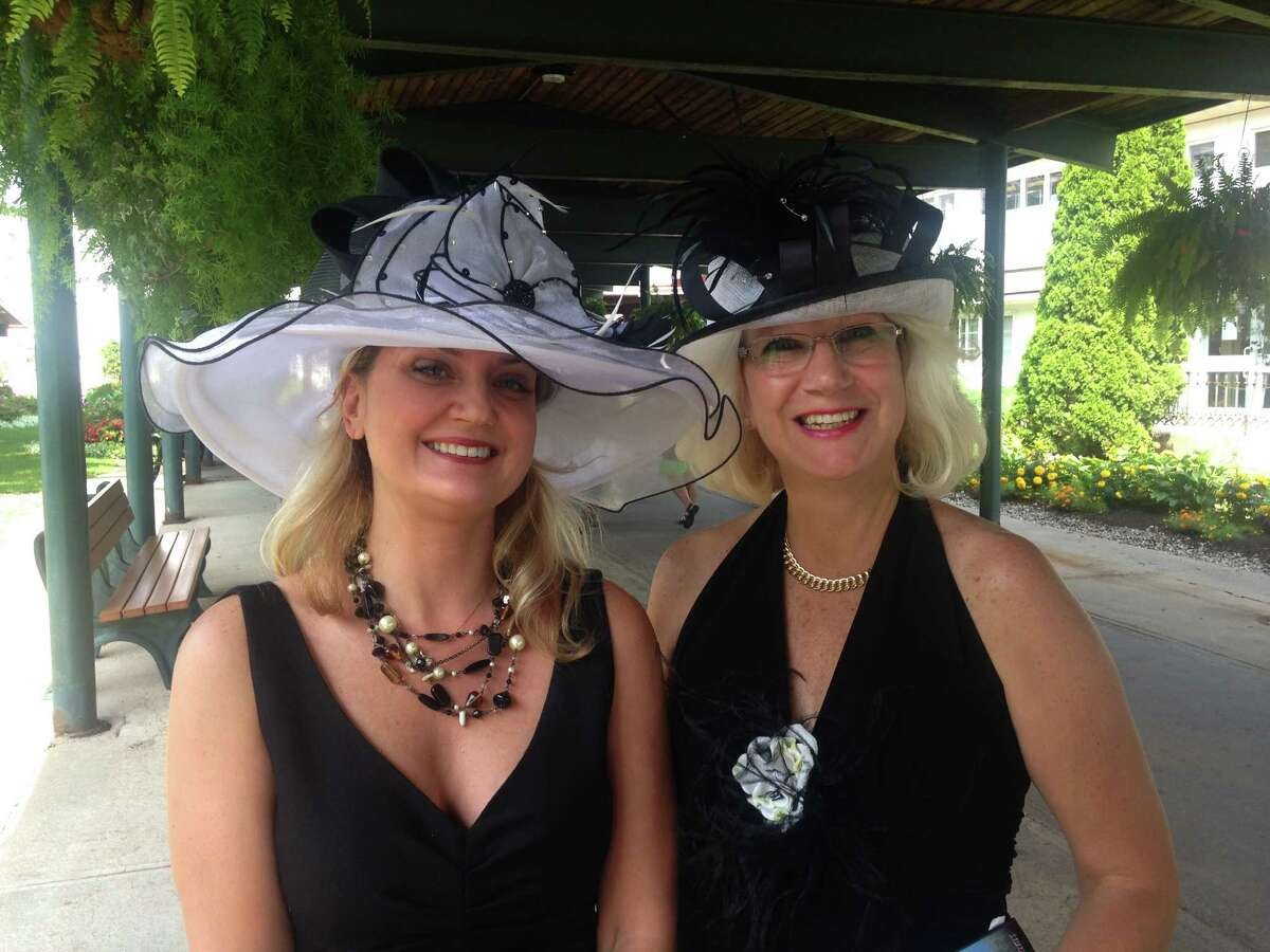 Dressed in their Travers finest, Amy O'Connor, left, and Cindy Doran, both of Troy, wait for a shuttle to the Saratoga Race Course from Saratoga Casino and Raceway, where parking was free, on Saturday, Aug. 29, 2015. (Photo by Steve Barnes/Times Union.)
