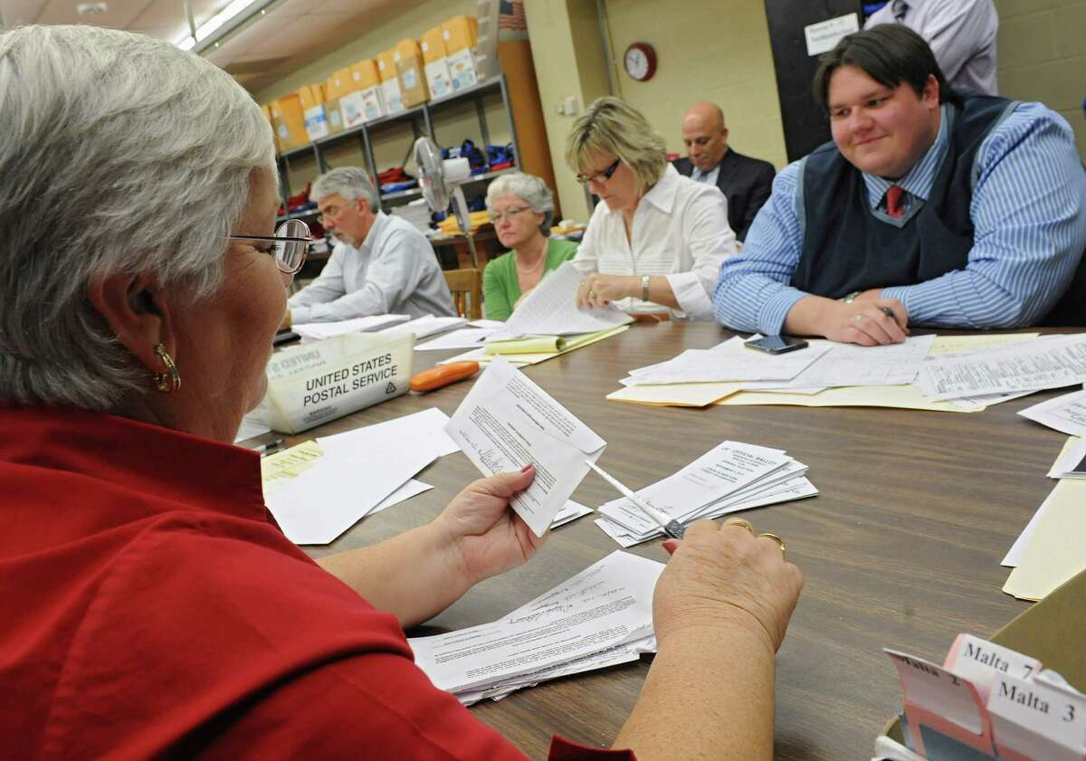 Bryon McKim, an attorney hired by the GOP, right, waits for the results at the Saratoga County Board of Elections as Cindy Wade, Republican senior clerk, left, opens absentee ballots on Wednesday, Nov. 13, 2013, in Malta, N.Y. (Lori Van Buren / Times Union archive)